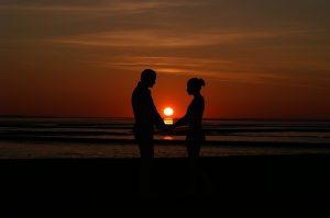 Heiraten auf Rhodos – Wenn die Hochzeit mit der Hochzeitsreise kombiniert wird! - Eine Person, die auf einem Strand mit einem Sonnenuntergang im Hintergrund steht - Valentinstag